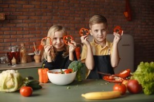Canva – Children in the Kitchen Holding Slices of Capsicum (1)